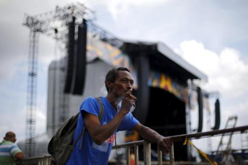 Un hombre fuma un puro mientras se monta el escenario de los Rolling...