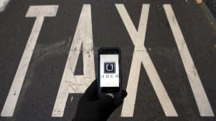 Ilustración del logo de la aplicación de smartphone Uber encima de...