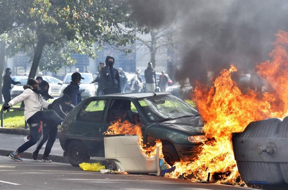 Unos manifestantes empujan un coche contra unos contenedores ardiendo...