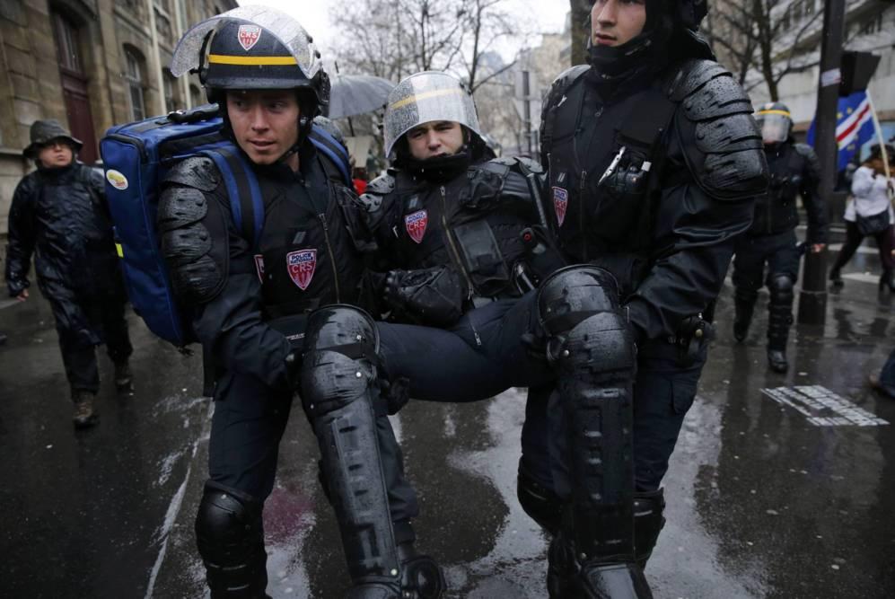 Varios policías evacuan a un compañero tras los disturbios con...