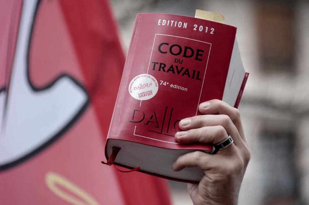 Un manifestante muestra un ejemplar del código de derecho laboral...