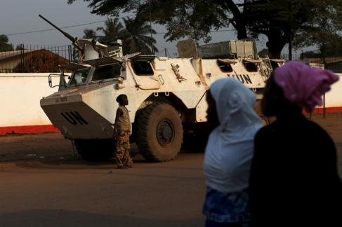 Dos mujeres caminan cerca de un vehículo de los cascos azules en...