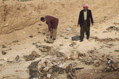 Dos hombres yasidistas buscan entre los restos de la fosa común de...