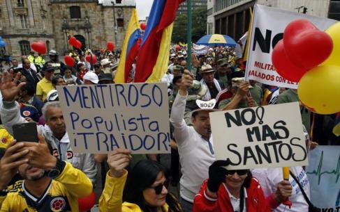 Manifestantes participan en una marcha contra el presidente Santos, en...
