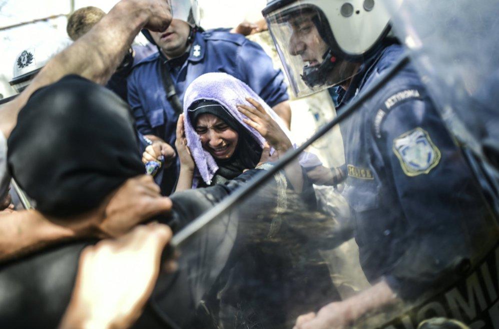 Una mujer se protege durante un forcejeo entre migrantes y agentes de...
