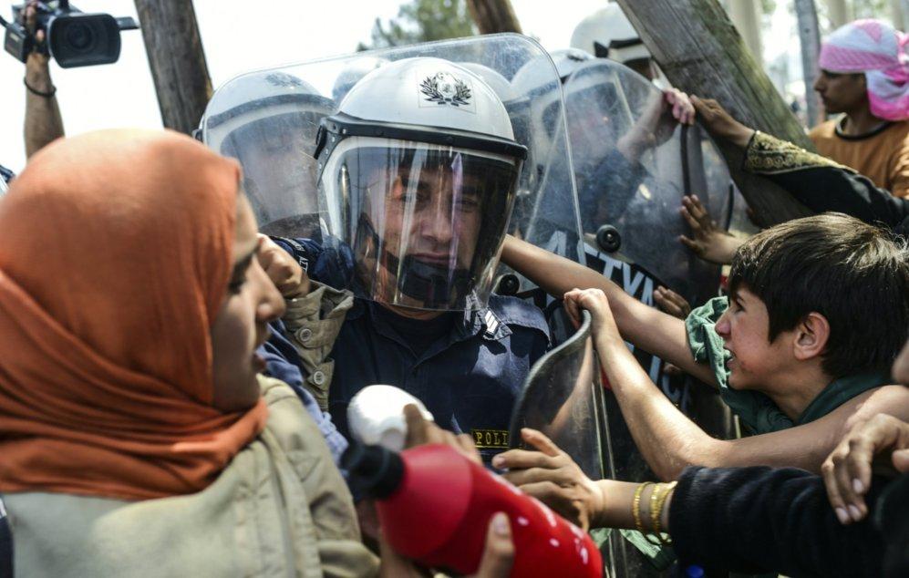 Agentes de policia tratan de contener a los migrantes que protestan...
