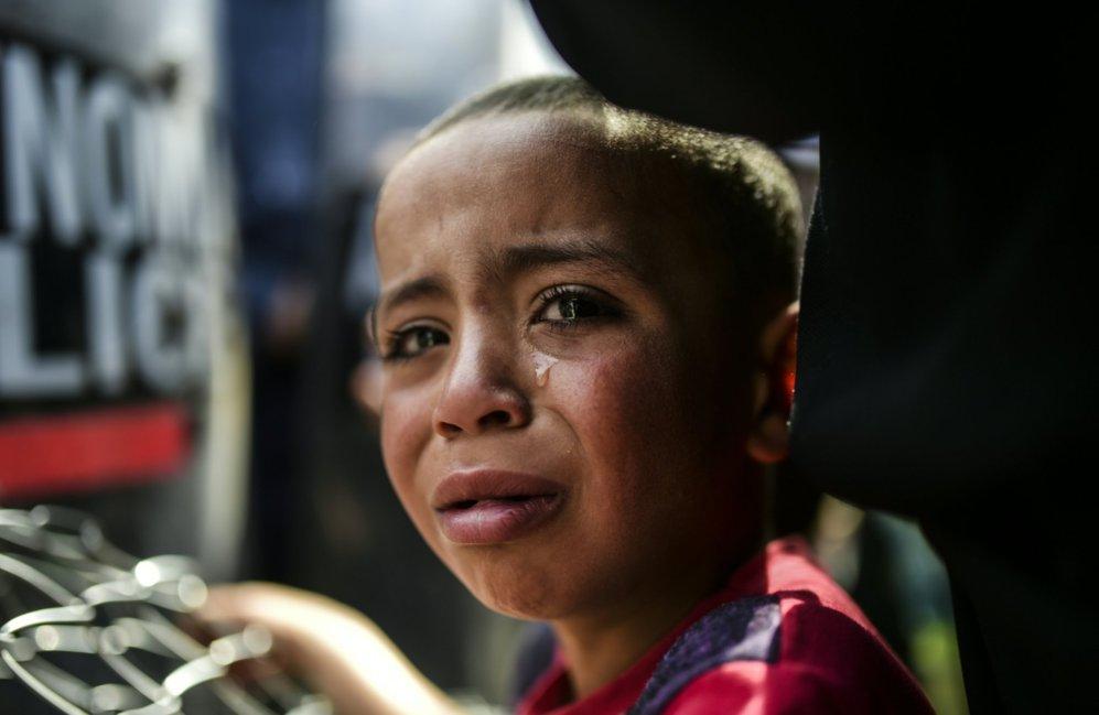 Un niño llora durante las protestas de migrantes y refugiados en la...