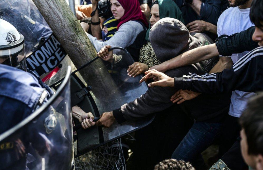 Varios migrantes y refugiados forcejean con los agentes de policia en...