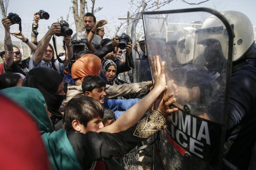 Mujeres y niños increpan a los policías antidisturbios que tratan de...