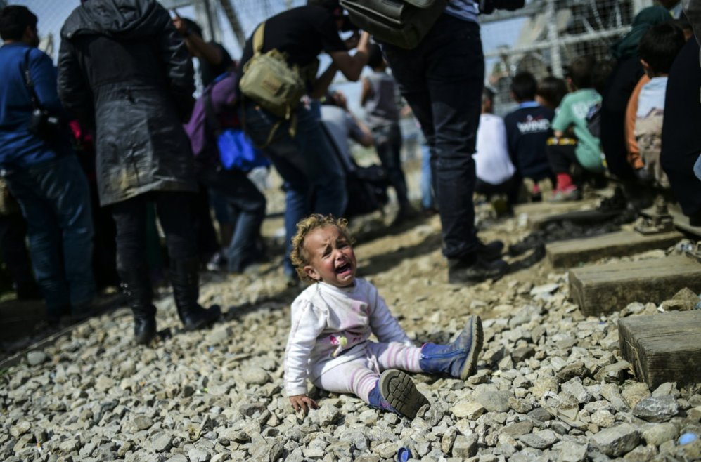 Una niña llora durante los forcejeos entre migrantes y agentes de...