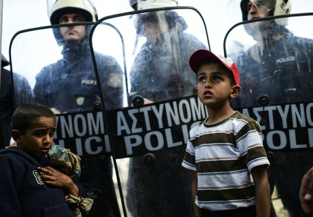 Dos niños junto a los agentes antidisturbios que tratan de contener...