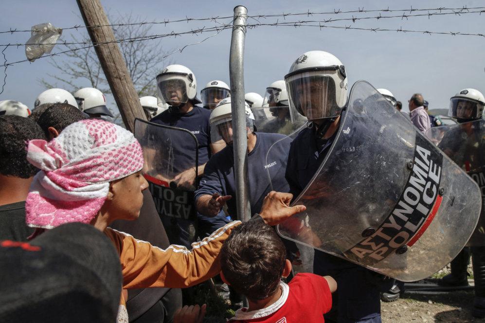 Un niño agarra el escudo de un agente durante uno de los momentos de...