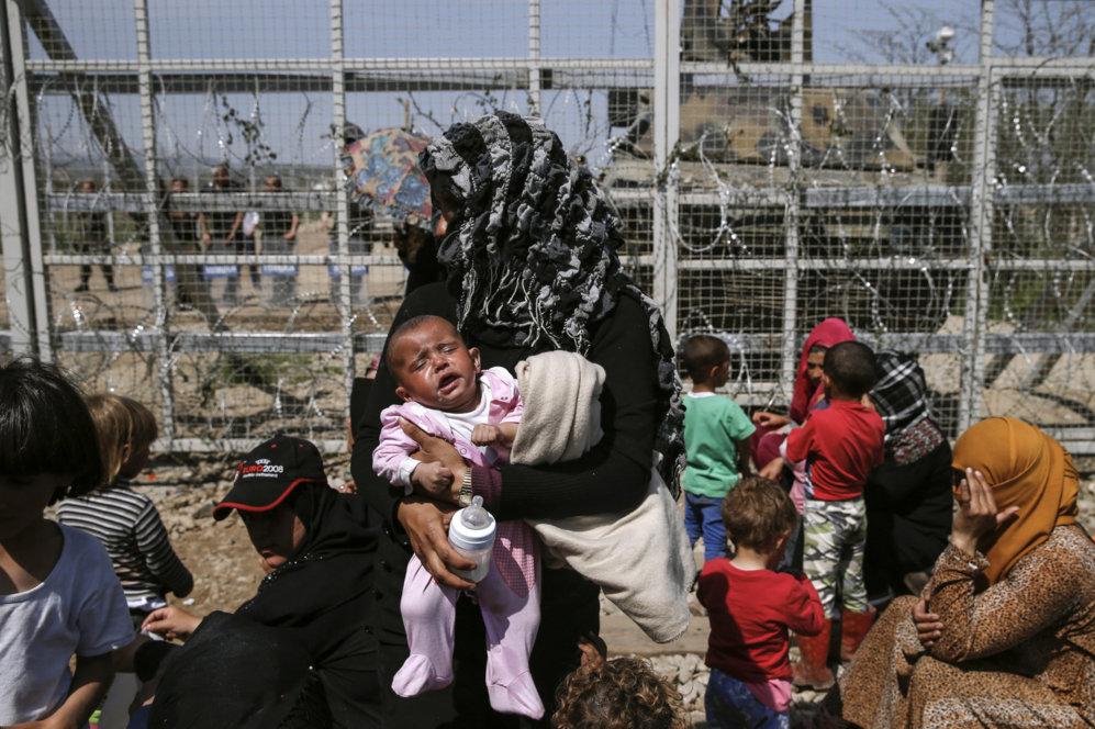 Una mujer sostiene a su bebé junto a la frontera protegida por...