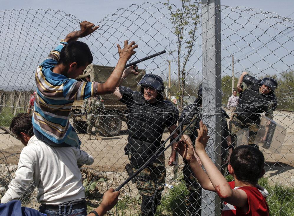 Un policía macedonio usa su porra para impedir que unos niños salten...