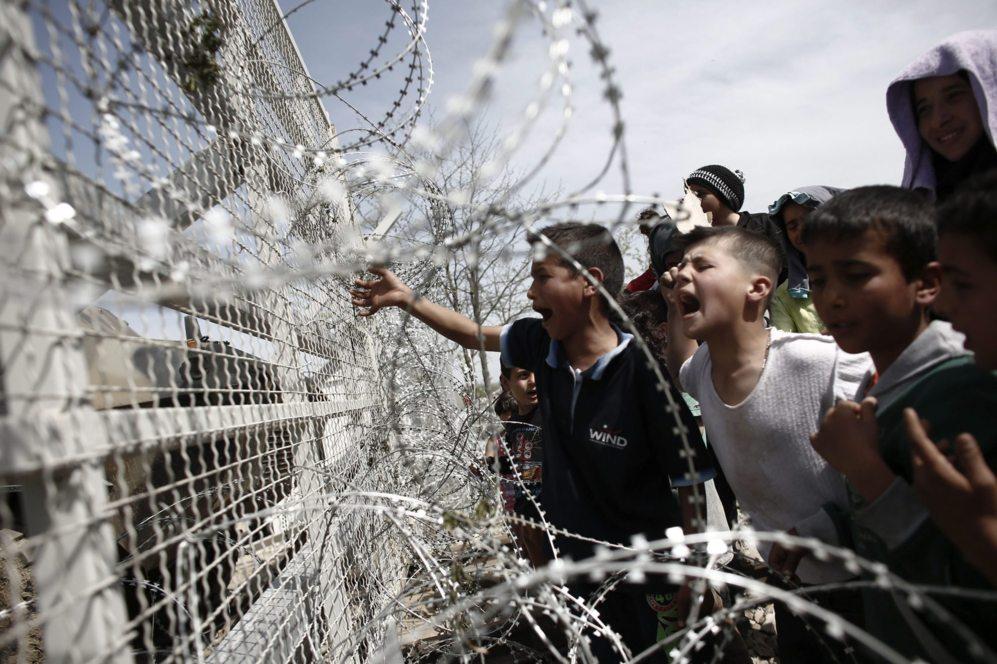 Varios niños increpan a los policías macedonios a través de las...