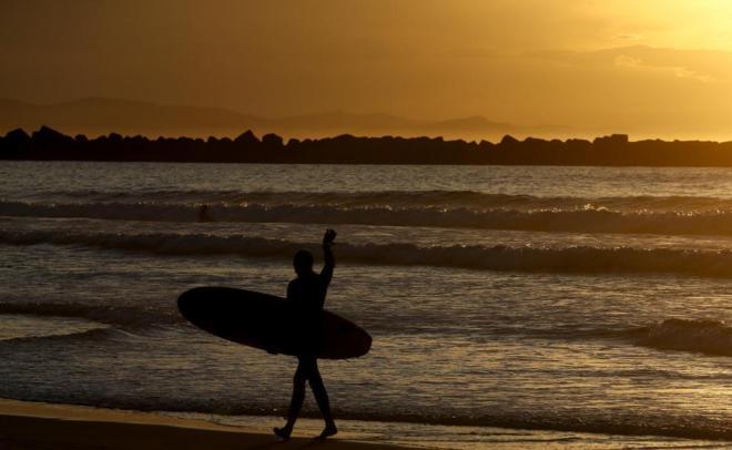 Un surfista sale del agua en la playa de la Zurriola de San Sebastián...