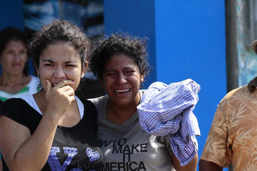 Dos mujeres lloran por los muertos en la localidad de Pedernales...