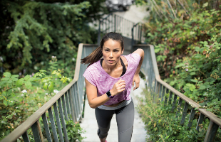 Chica corriendo con reloj inteligente Fitbit