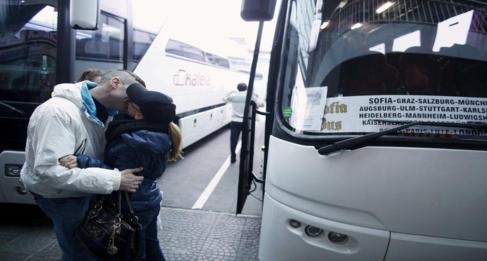 Una pareja se besa en una estación de autobuses.