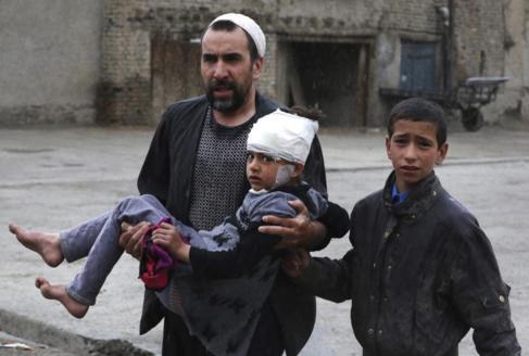 Un hombre lleva a una niña en brazos herida tras el atentado cerca...