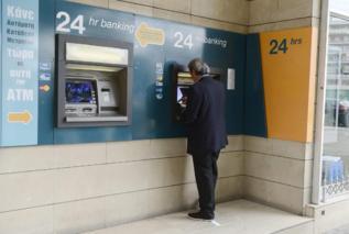 Un hombre saca dinero de un cajero en Chipre