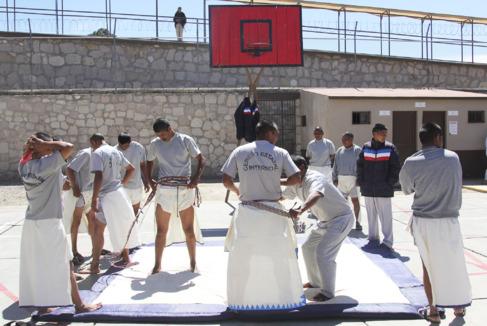 Presos del penal Cereso 8 practican la lucha raramuri en el patio.