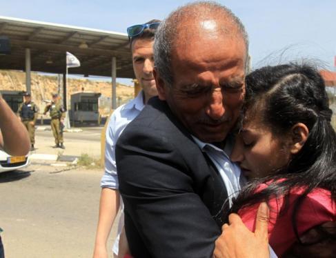 El padre de la niña palestina liberada, Dima al-Wawi, abraza a su...