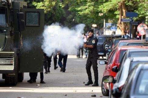 Un policía lanza gases lacrimógenos contra los manifestantes en El...
