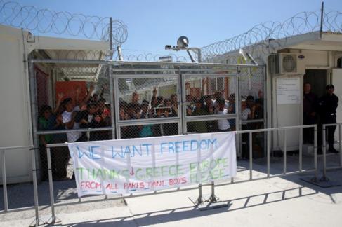 Varios refugiados se acercan a las vallas del centro de Moria el 16 de...