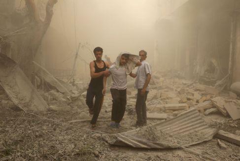 Dos personas ayudan a un herido en un bombardeo en Fardous, un barrio...
