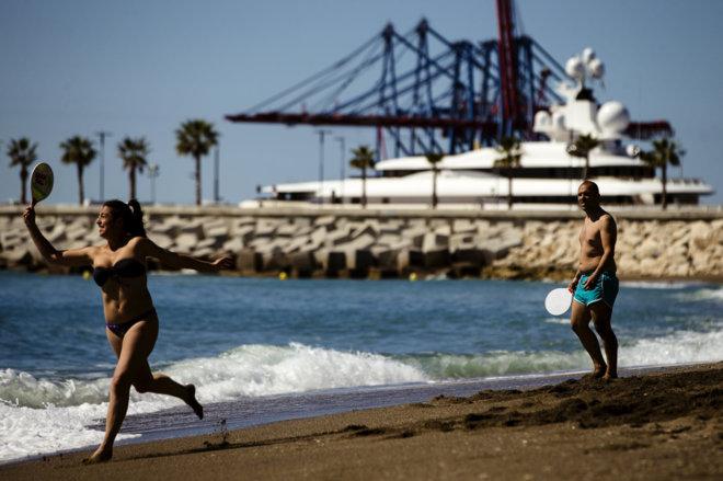 Dos personas juegan a las palas en la playa de la Malagueta (Málaga).