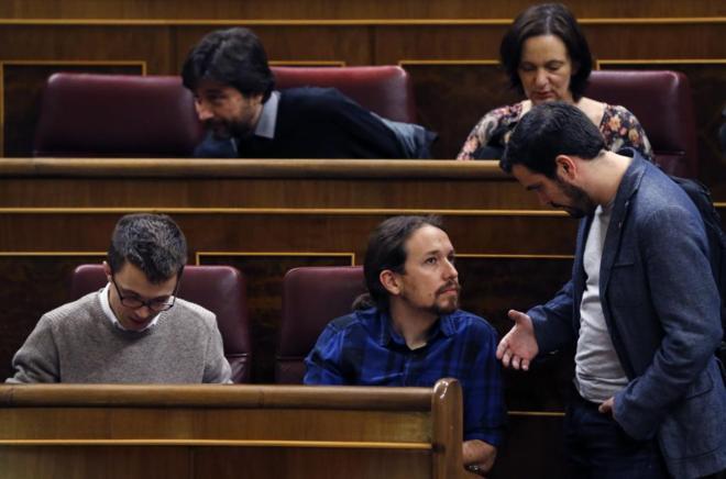 Alberto Garzón y Pablo Iglesias hablan en un pleno del Congreso.