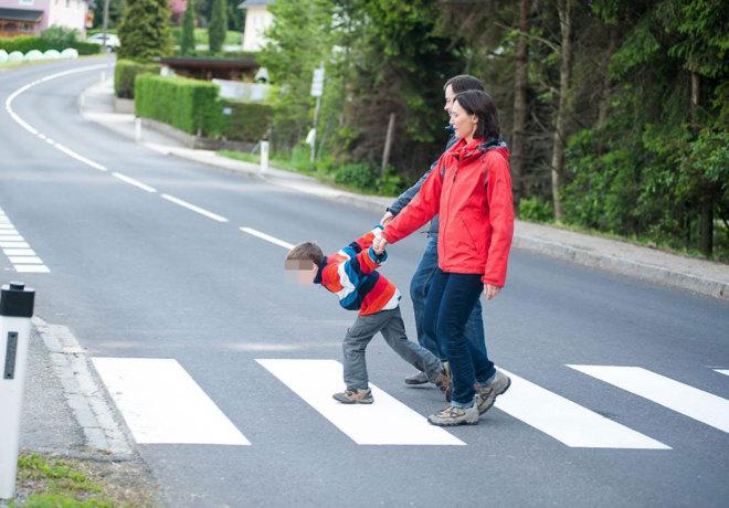 Un niño con hiperactividad cruza la calle de mano de sus padres.