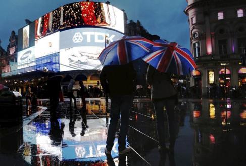 Gente se resguarda de la lluvia en Piccadilly Circus, en Londres