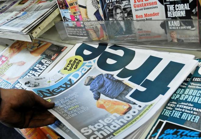 Un lector coge un ejemplar del periódico 'The New Day' en un quisoco...