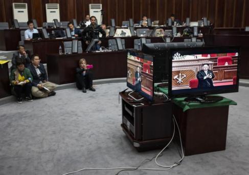 Periodistas extranjeros siguiendo el discurso de Kim en una sala de...