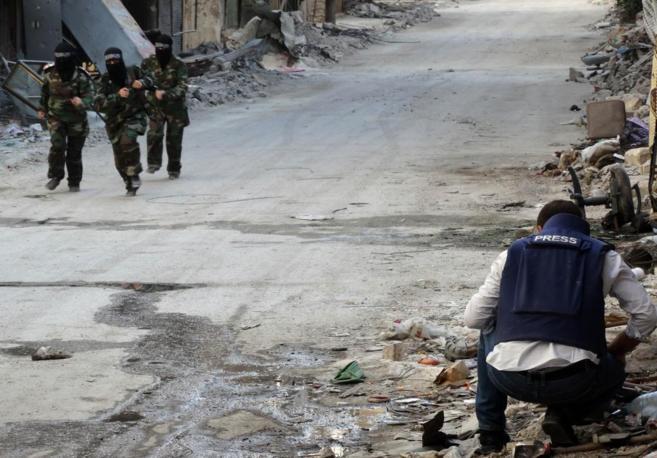 Un periodista observa a un grupo de milicianas en la ciudad siria de...