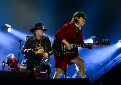 Axl Rose, sentado y con sombrero, junto a Angus Young en Lisboa.
