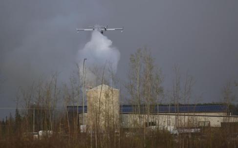 Un avión sobrevuela Fort McMurray lanzando agua contra las llamas.