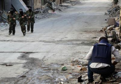 Un periodista observa a unas milicianas en Alepo.