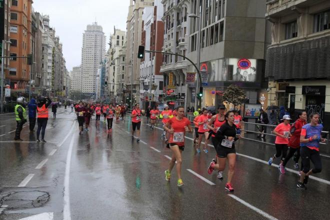 Participantes en la Carrera de la Mujer en Madrid, bajo la lluvia.