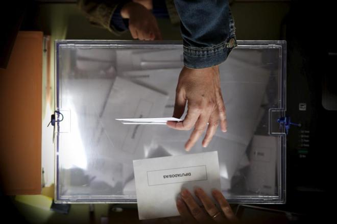 Un ciudadano español deposita su voto en la urna en las elecciones...