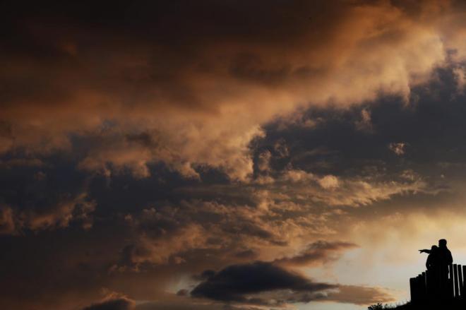 Una pareja observa la puesta de sol sobre la capital navarra.