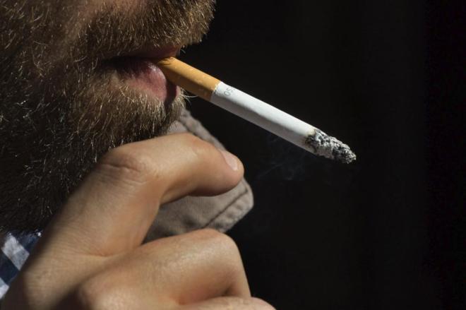 Un hombre fumando un cigarrillo.