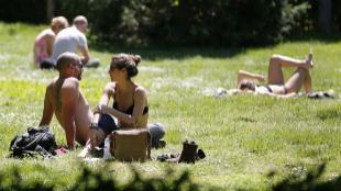 Varias personas toman el sol en el Parque del Retiro, en Madrid.