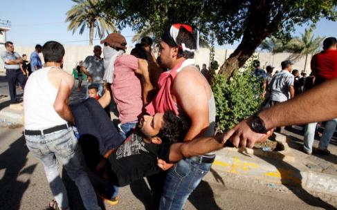 Varios manifestantes trasladan a un herido en Bagadad