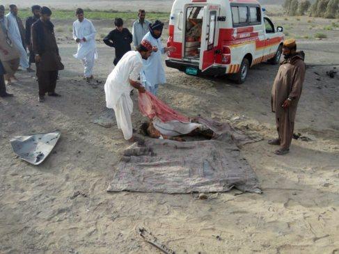 Un grupo de afganos retira un cuerpo tras el ataque aéreo de EEUU que...