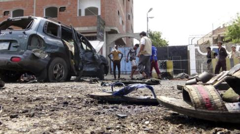 Varias personas inspeccionan el lugar de un atentado suicida en la...