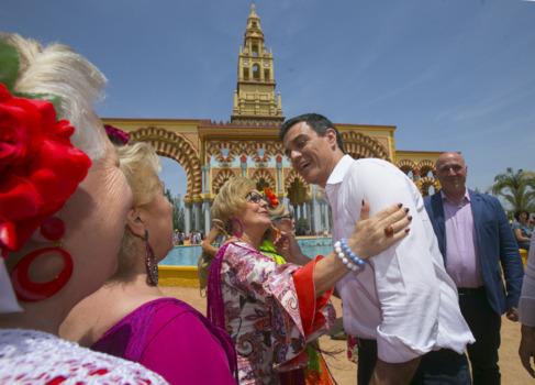 Pedro Sánchez saluda a unas mujeres de flamenca durante su visita a...