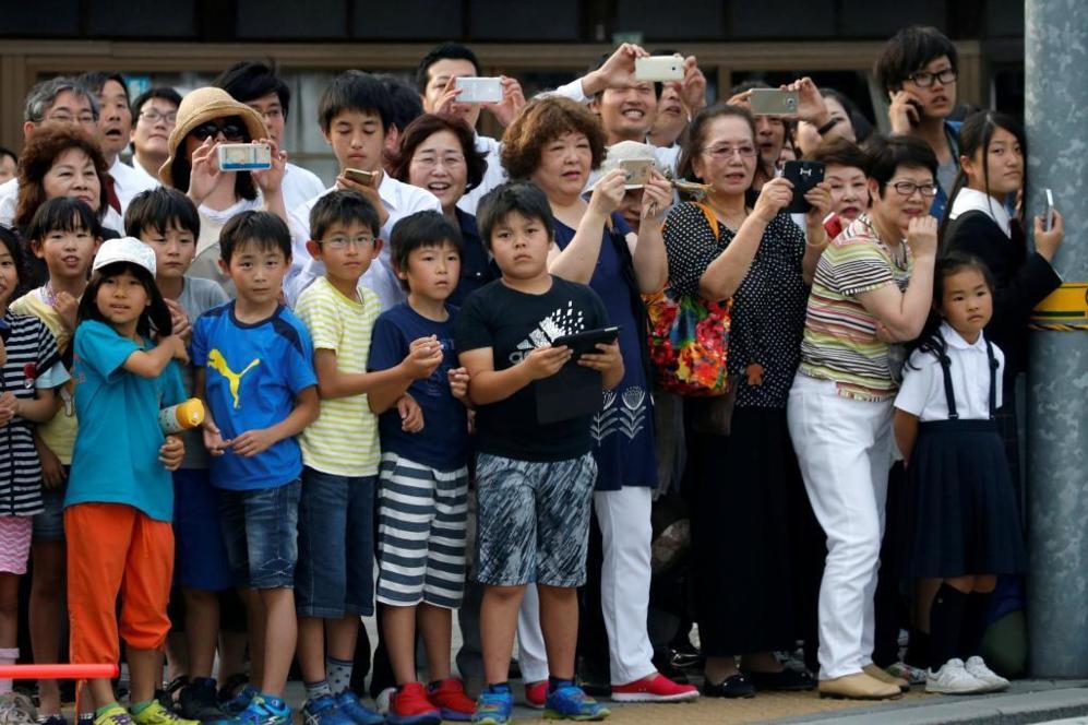Residentes de Hiroshima miran el vehículo del presidente Barack...